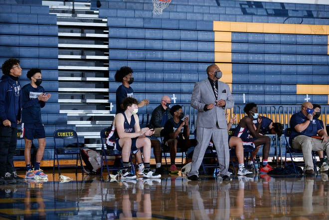 The East Lansing bench and coach Ray Mitchell watch against Grand Ledge, Thursday, Feb. 11, 2021, in Grand Ledge, Mich. East Lansing won 52-50.
