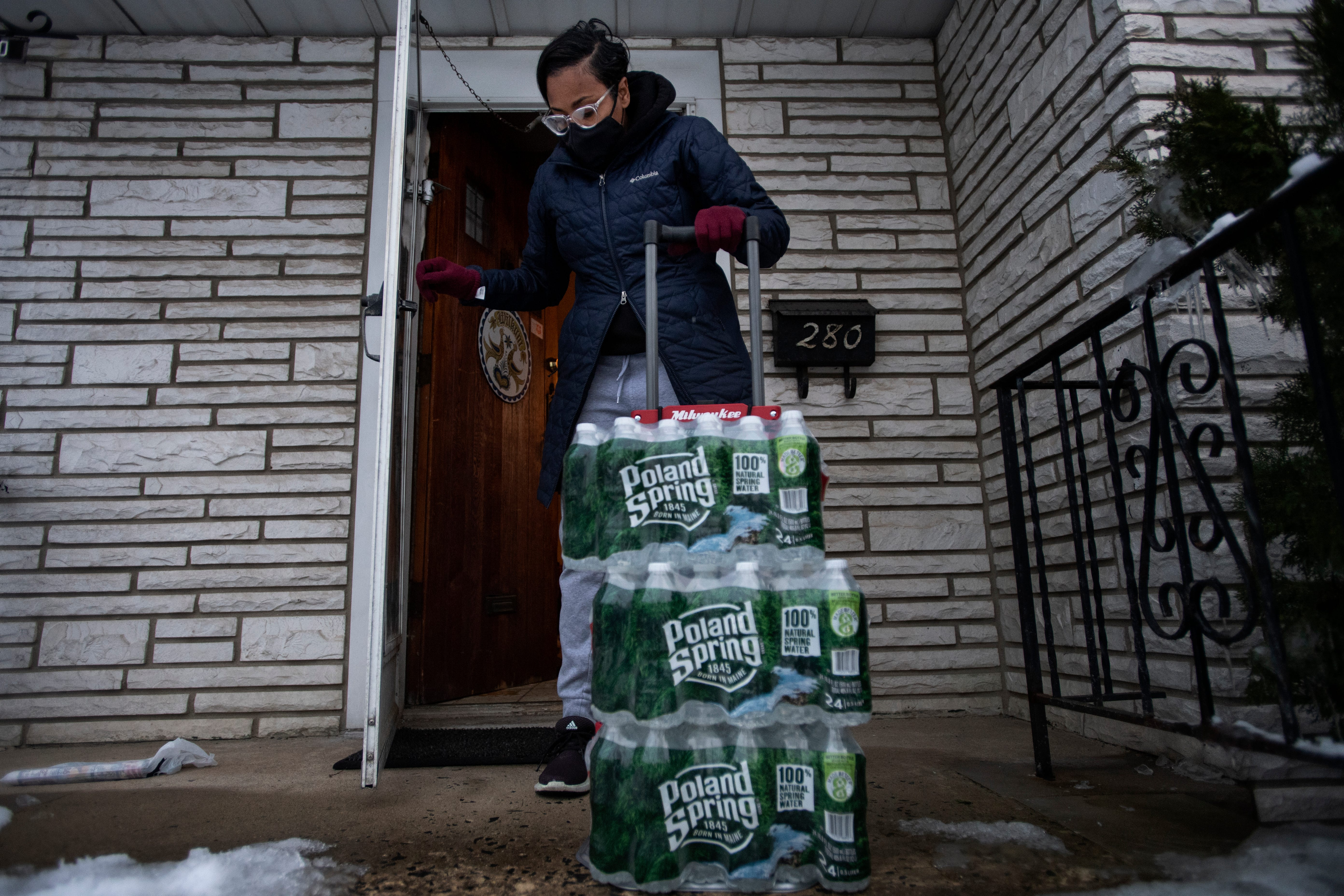 Shakima Thomas, of Newark, brings bottled water into her home on Thursday, February 11, 2021. Thomas became an activist for clean water after learning her son Bryce, 6, had lead in his blood. Thomas does not drink or cook with water from the faucets at her home because testing has shown lead in the water.