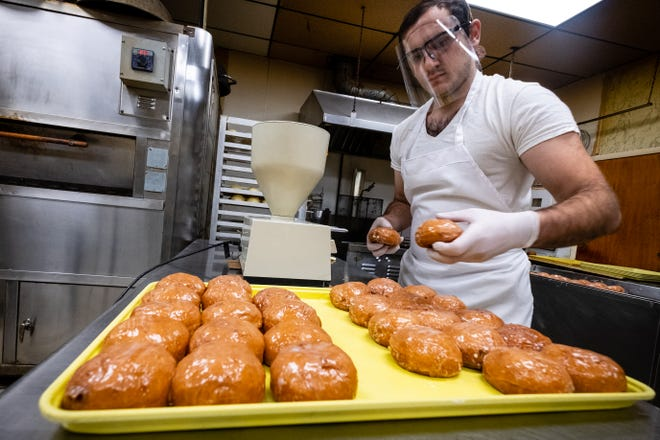 Baker Mike Momirovski fills paczki with custard Thursday, Feb. 11, 2021, at Paul's Bakery in Marine City.