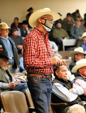 A masked man stands in the buyers section during the final sale at the Shasta Livestock Auction Yard on Friday, Feb. 12, 2021.