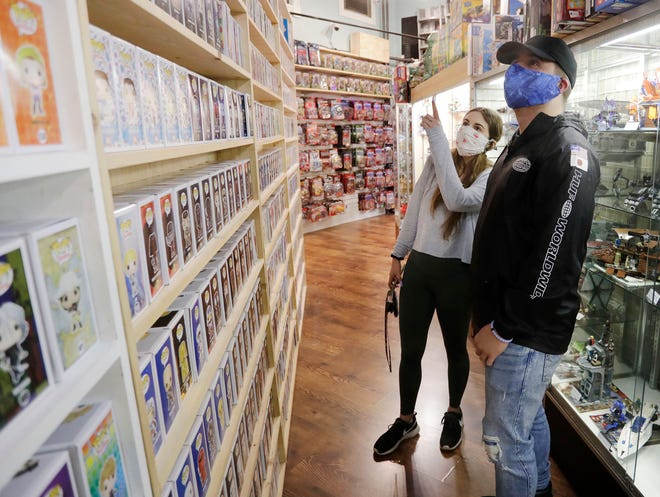 Marissa Schroeder, left, and Eli Mayer, both of Sheboygan, both masked due to COVID-19, check over some merchandise at Freaktoyz, Monday, May 18, 2020, in Sheboygan, Wis.
