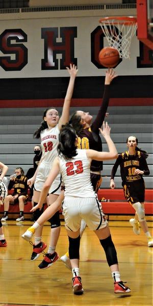 Berne Union's Bella Kline drives through Jenna (10) and Makaela McLaughlin (23) in Thursday's game. The Rockets won 49-27.