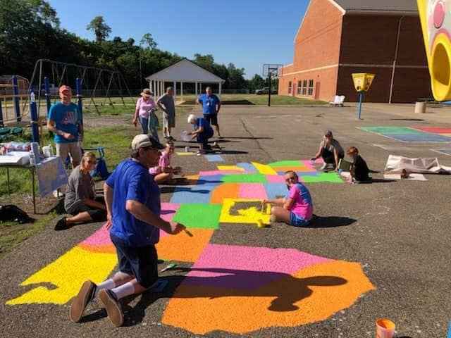 Painting U.S. maps on playground for local school children has long been an outreach program of the Kiwanis Club of Zanesville, celebrating its 100th anniversary this year.
