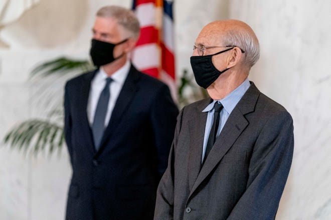 Justices Neil Gorsuch, left, and Stephen Breyer pay their respects at a private ceremony for Justice Ruth Bader Ginsburg at the Supreme Court on Sept. 23, 2020.