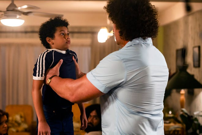 "Andre the Giant (Matthew Willig) lifts a young Dwayne Johnson (Adrian Groulx) in the debut episode of ""Young Rock."""