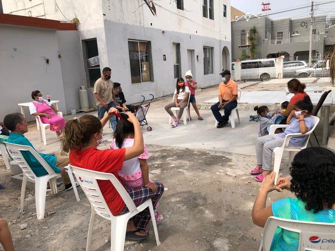 Migrants at El Buen Samaritano shelter in Nuevo Laredo, Mexico, listen to Pastor Lorenzo Ortiz share the latest news on President Joe Biden's immigration directives.