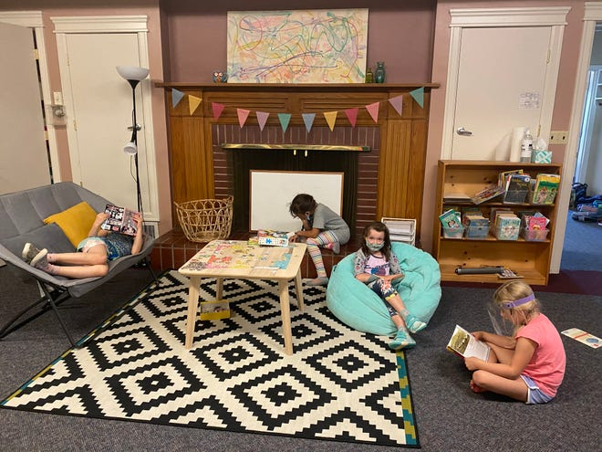 Some school-age children take a reading break at a Small Wonders School center in Portland, Ore. When the school reopened with fewer toddlers and preschoolers, co-owner Allison Morton added a program for elementary school children.