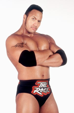 "Dwayne Johnson flexes the People's Eyebrow as his wrestling persona ""The Rock"" in 1999."