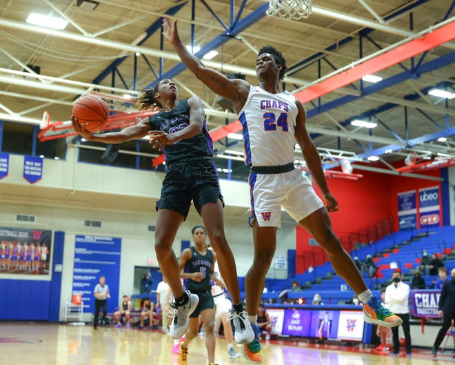 Westlake senior KJ Adams goes for the block against San Marcos guard Malik Presley in the second quarter of action Feb. 12 at Westlake High School. Westlake secured the district championship in the 90-72 final over the Rattlers.