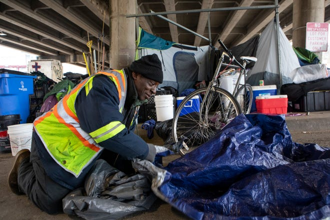 XL Jefferson Jr., 58, rolls up an extra tarp Saturday after repairing the tent of another person experiencing homelessness. Jefferson said he has prepared his tent to keep him warm over the next few days as temperatures continue to drop.