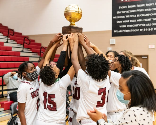 Weiss players celebrate with the trophy after the Wolves' 57-31 victory over Anderson in a Class 5A first-round playoff game Friday at Weiss High School. The playoff win was the first in school history  for Weiss.