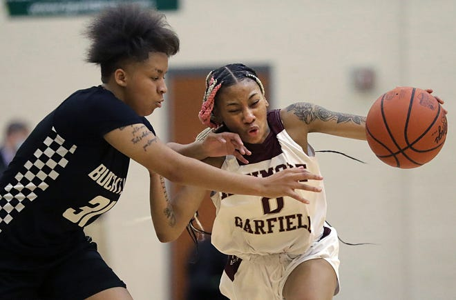 Kenmore-Garfield's I'Anna Lopp, right, drives to the basket against Buchtel's Amiyah Stallings during the first half of the Griffins' 56-54 overtime win over the Rams in the City Series championship game. [Jeff Lange/Beacon Journal]