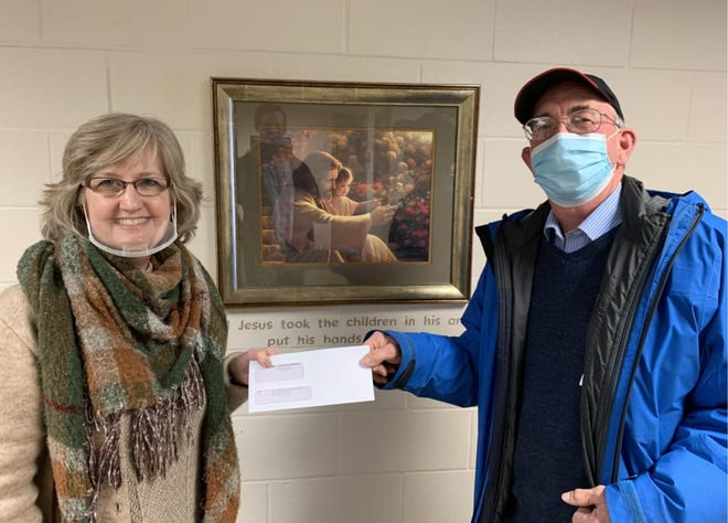 Sherry Bouquet, executive director of Fostering Family Ministries, accepts a grant from Kenny Obleholtzer, Trinity Outreach Fund Committee member.