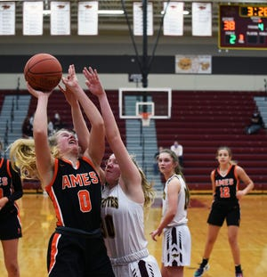 Ames forward Ireland Buss tries to muscle up a shot against Ankeny's Abigail Johnson during the Little Cyclones' 45-32 loss to the Hawks Friday at Ankeny.