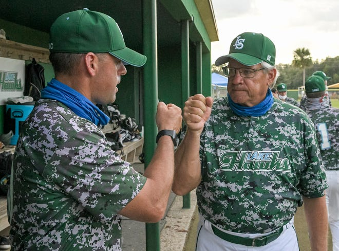 Lake-Sumter State College head baseball coach Rich Billings, left, and his father, Rich Billings. share a fist bump after the Lakehawks beat South Florida State College Wednesday at the LSSC baseball complex in Leesburg. [PAUL RYAN / CORRESPONDENT]