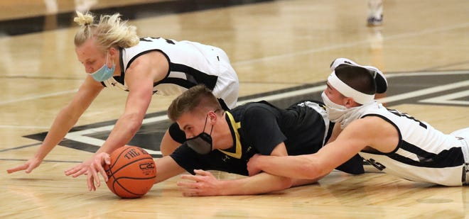 Kobe Haglund (left) and Blake Bosma (right) diver for a loose ball with Grand Haven's Owen Worthington on Friday at West Ottawa.