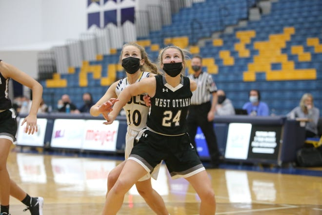 West Ottawa's Grace Pedersen fights for position with Grand Haven's Avery Keefe on Friday.