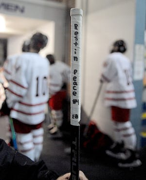 The Holliston High School hockey team memorializes former team captain Ethan Bagge on their sticks at a game against Dover-Sherborn/Weston on Feb. 12, 2021, at Loring Arena in Framingham.