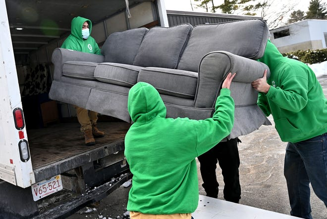 Members of Holliston-based Green Team Junk Removal load a sofa into a truck at the Fresh Start Furniture Bank in Hudson, Feb, 13, 2021. The sofa and its delivery was donated to Hudson resident Bobbie Jo Labarre, the victim of an apartment fire in December.