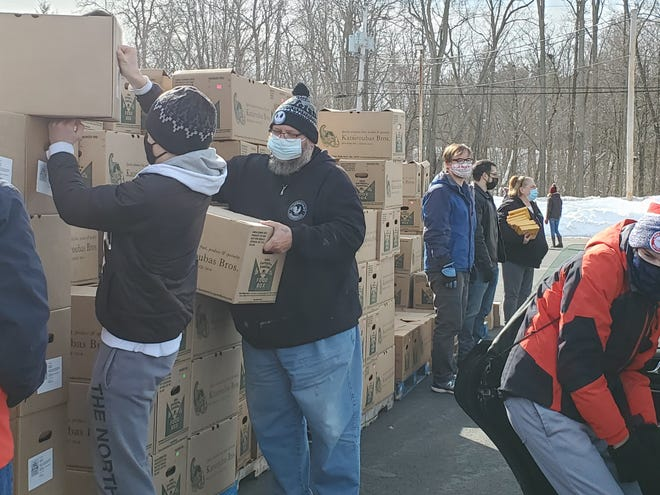 Volunteers from Restoration Church in Dover fill the trunks and backseats of cars with boxes of food. The free food distribution will continue through April, every Saturday.