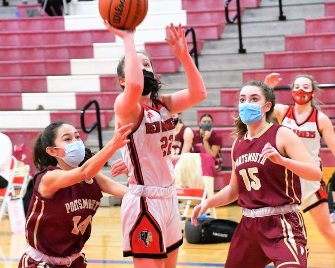 Spaulding's Mackenzie Brochu, center, twists to the basket between Portsmouth's Bella Stover, left, and Margaret Montplaisir during Division I action Friday in Rochester.
