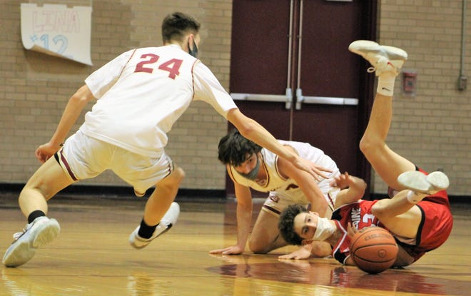Portsmouth's Kevin Cummings (24) and Carmine Zingariello battle Spaulding's Jack Sullivan for loose ball at midcourt during the third quarter.