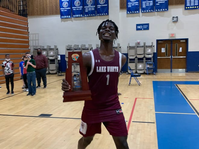 Lake Worth's Maurice Campbell celebrates with the Class 7A-District 11 trophy on Friday after the Trojans beat Santaluces 60-59 on a last-second free throw.