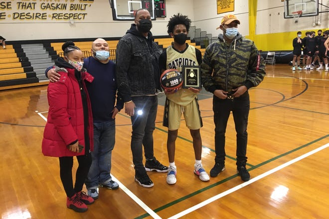 Raheim Rainey poses with his family moments after hitting a 3-pointer that put him past 1,000 career points for Davies. Rainey finished the game with 30 points, leading the Patriots to an 82-63 victory over Prout.