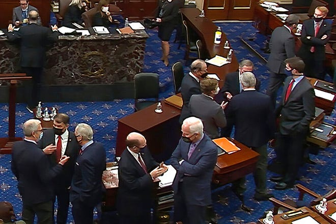 In this image from video, Republican senators and staff talk on the floor after a vote on the motion to allow witnesses in the second impeachment trial of former President Donald Trump in the Senate at the U.S. Capitol in Washington, Saturday, Feb. 13, 2021. (Senate Television via AP)