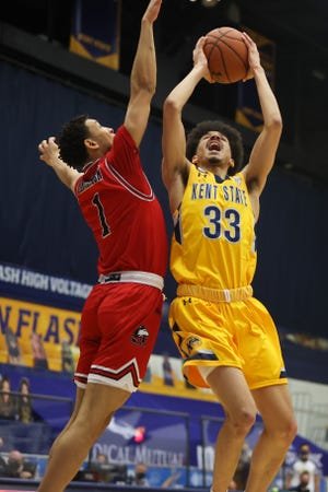 Kent State guard Jeremiah Hernandez leaps up to score against Northern Illinois junior guard Trendon Hankerson during Saturday's game against Northern Illinois University at the M.A.C. Center.