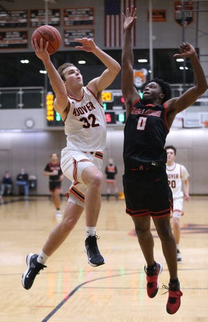 Brock Henne (32) of Hoover goes to the basket while being guarded by Kobe Johnson (0) of McKinley during their game at Hoover on Friday, Feb. 12, 2021.