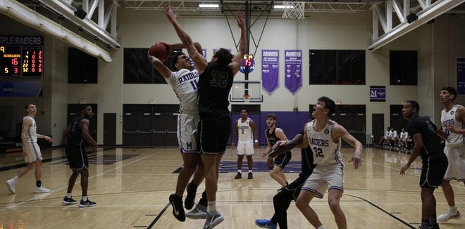 Mount Union freshman Christian Parker (11) goes up for a shot during Friday's game against Heidelberg