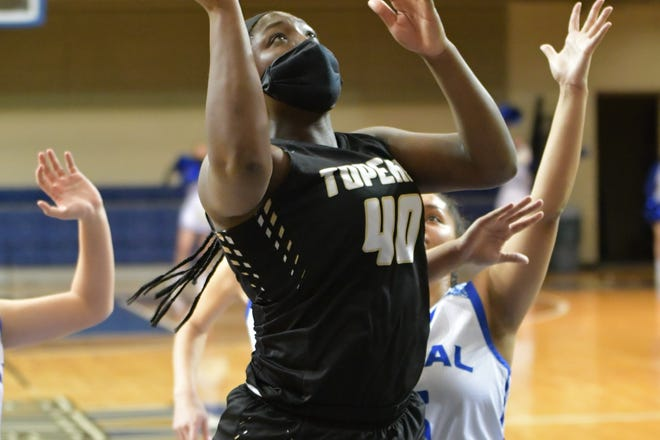 Topeka High's NiJaree Canady goes in for a shot attempt during Friday's huge Centennial League showdown between the top-ranked Trojans and No. 3 Washburn Rural. Canady scored 19 points and had 20 rebounds and came up with a big steal late as High rallied from down six with 15 seconds left to pull out a 59-53 overtime win.