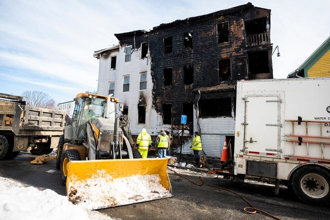 Worcester Department of Public Works and Parks crews turn off the water supply at 11-13 Jaques Ave. on Saturday, where a deadly fire broke out Friday night.