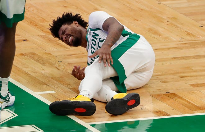 Celtics guard Marcus Smart grabs for his left calf after being injured during the fourth quarter against the Lakers on Jan. 30.