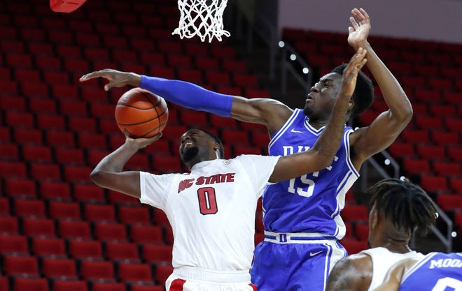 N.C. State's D.J. Funderburk (0) shoots as Duke's Mark Williams (15) defends during the first half of N.C. State's game against Duke at PNC Arena in Raleigh, N.C., Saturday, February 13, 2021.