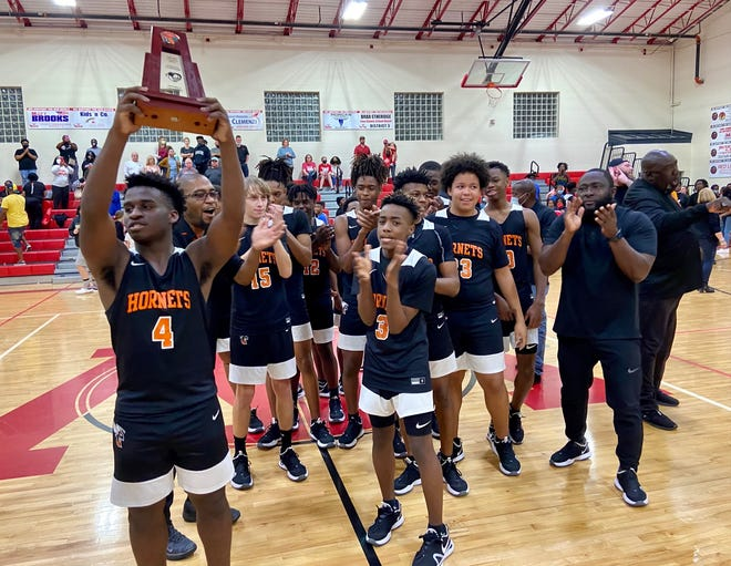 Hawthorne senior Dre Lawrence hoists the District 7-1A championship trophy after the Hornets beat Williston in the district tournament final Friday night at Williston High School.