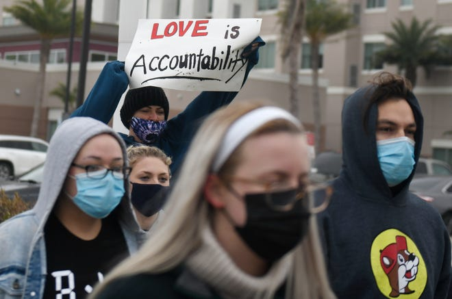 """Heather Shields holds a """"Love is accountability"""" sign during the """"Support for Breonna's Law"""" rally, Saturday, Feb. 13, 2021. Protesters walked from Cole Park to City Hall."""