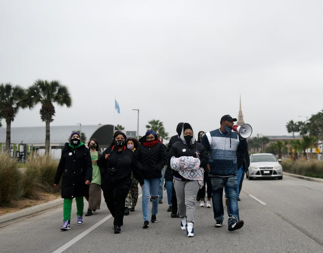 """Protesters, including Breonna Taylor's mother Tamika Palmer, second from right; attend the """"Support for Breonna's Law"""" rally, Saturday, Feb. 13, 2021. Breonna's Law bans """"no knock"""" search warrants and for police officers to wear body cameras before executing a search warrant."""