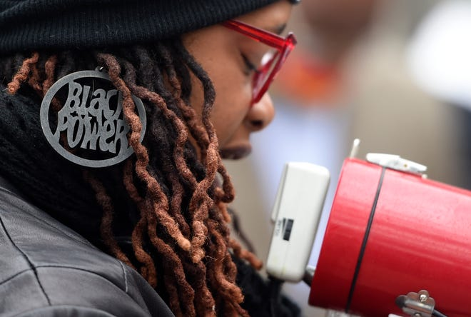 """Khalilah Collins wears """"Black power"""" earrings while speaking during the """"Support for Breonna's Law"""" rally, Saturday, Feb. 13, 2021. Collins traveled from New Orleans for the event."""