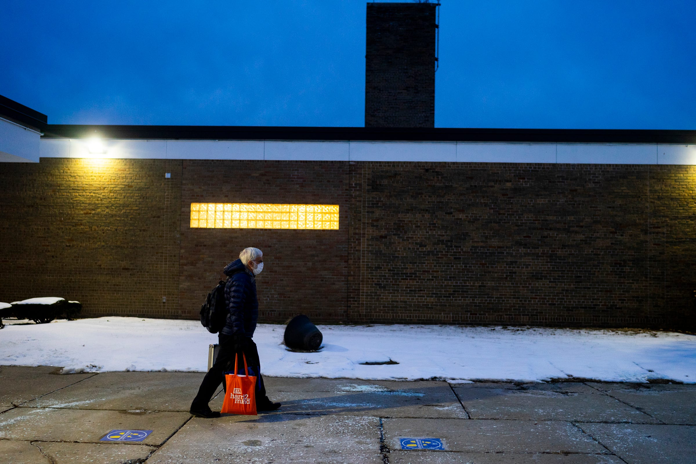 """Christopher Holstein walks to his car just before 6 p.m. after finishing a virtual practice for an upcoming competition in the Academic Games on Feb. 4, 2021 at Bates Academy in Detroit. """"A lot of teachers will retire this year. I'm not ready,"""" Holstein said. He an educator of 52 years and he's celebrating his 45th year as an Academic Games coach. """"It keeps me going."""""""