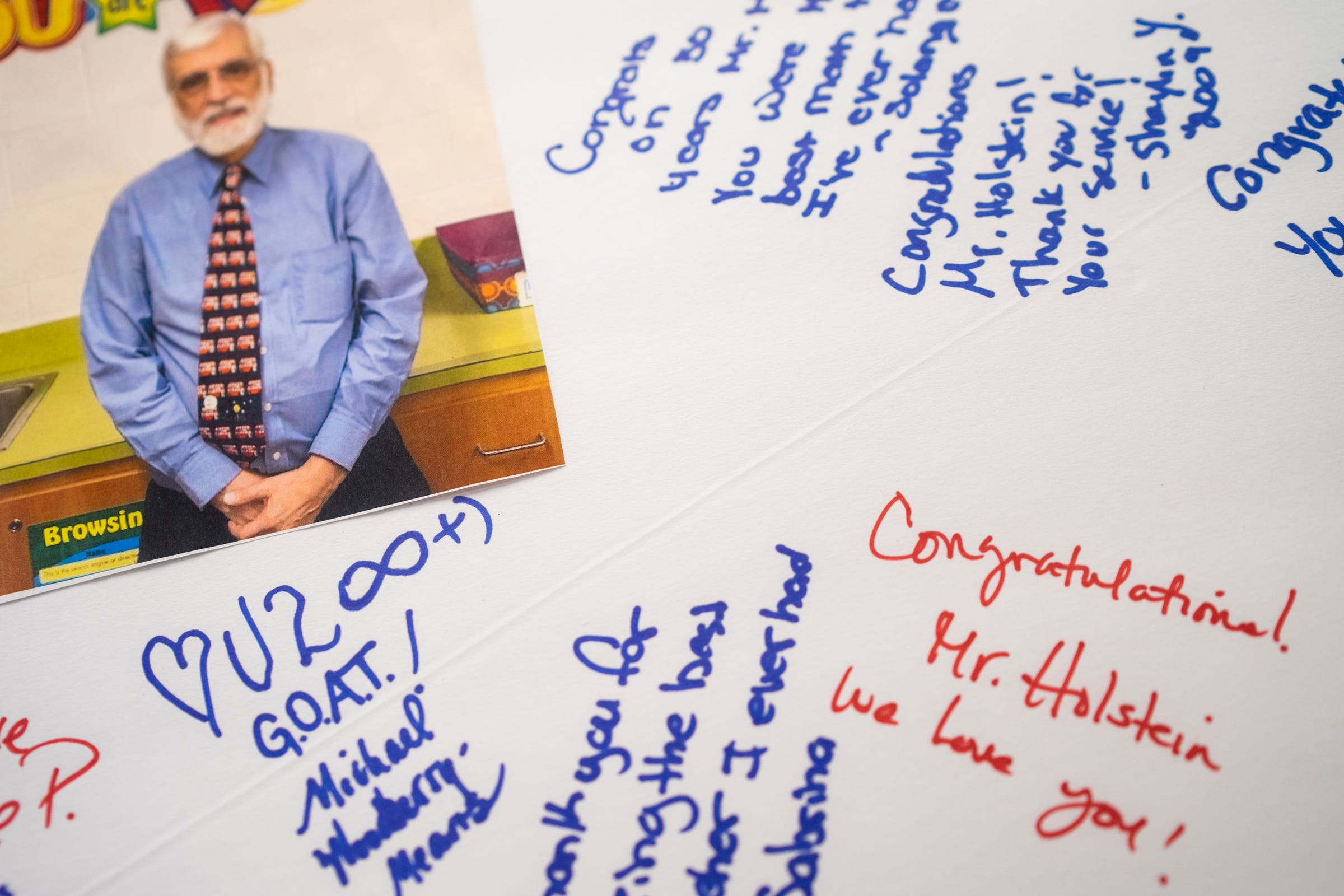 """Christopher Holstein received a poster from current and former students for his 50th year of teaching. Holstein, an educator of 52 years, is celebrating his 45th year as an Academic Games coach. """"It keeps me going,"""" Holstein said regarding the Academic Games."""