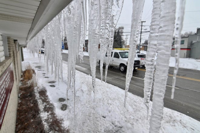 Huge icicles hang from a building along Crooks Road in Royal Oak as cold weather grips the Metro Detroit area on Saturday, February 13, 2021.