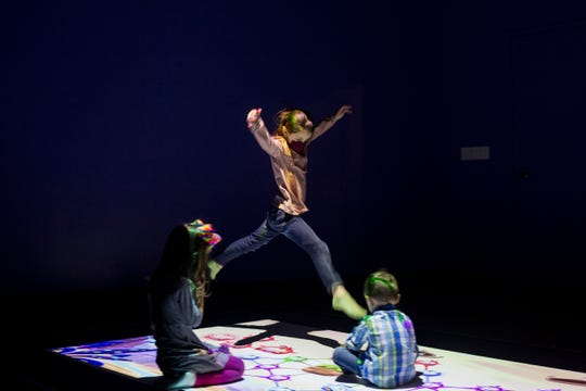 """Light is projected onto the floor as kids play on the new """"high-tech, low-touch"""" exhibit, Friday, Feb. 12, 2021, at the Iowa Children's Museum in Coralville, Iowa."""