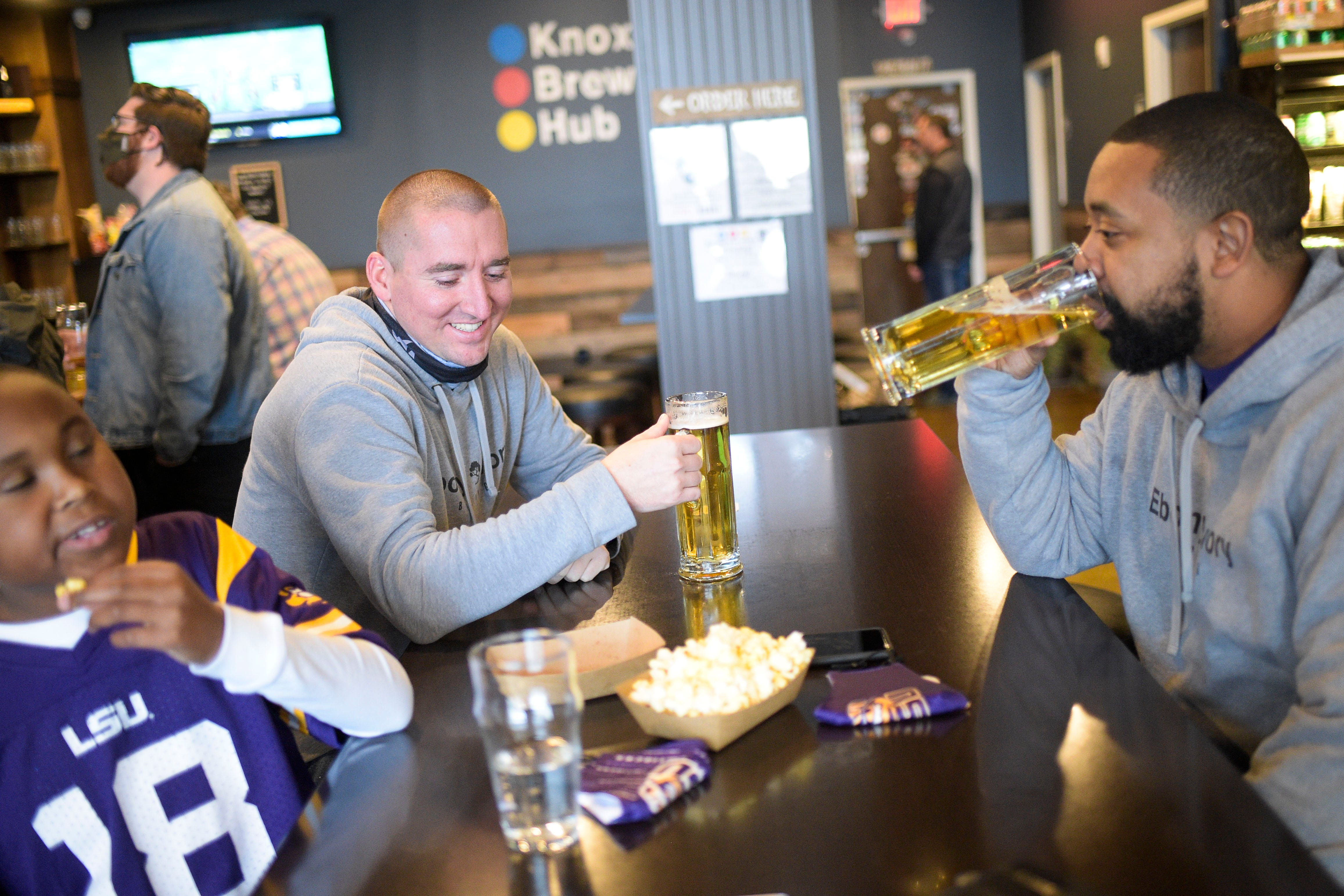 From left, Quincy Dupas, Mitchell Russell and Chico Dupas drink beer and eat popcorn at Knox Brew Hub in downtown Knoxville, Tenn. on Saturday, Feb. 13, 2021.
