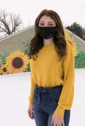 """Brighton High School class of 2018 graduate Hannah Palmer founded a new non-profit called the """"Sunflower Project"""" to help young people struggling with mental illness. Palmer poses in front of a mural of sunflowers in downtown Northville Friday, Feb. 12, 2021."""