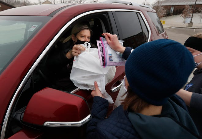 Sherry Townsend grabs two orders she got by placing an online order at St. Michael Catholic Church. 