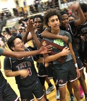 Tate's Jordan Williams holds the District 1-6A Championship trophy while celebrating with his teammates after a win over Milton on Friday.