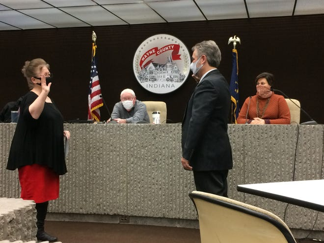 Wayne County Clerk Debbie Berry administers the oath of office to new Wayne Township Assessor Gary Callahan on Saturday in the Wayne County Administration building.