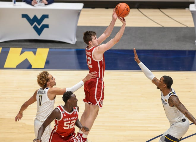 Austin Reaves shoots a three-pointer over Gabe Osabuohien during the first half.